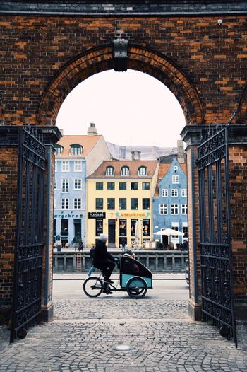 A typical cargobike, representing the bike culture in Copenhagen, in Copenhagen's most famous street Nyhavn, seen through a gate. Nyhavn Denmark cityscapes City Life City Street Bikes Arch Built Structure Bicycle Day Travel Travel Destinations People City