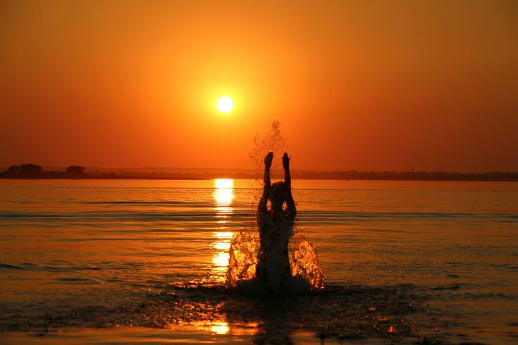Silhouette Woman In Enjoying In Sea At Sunset