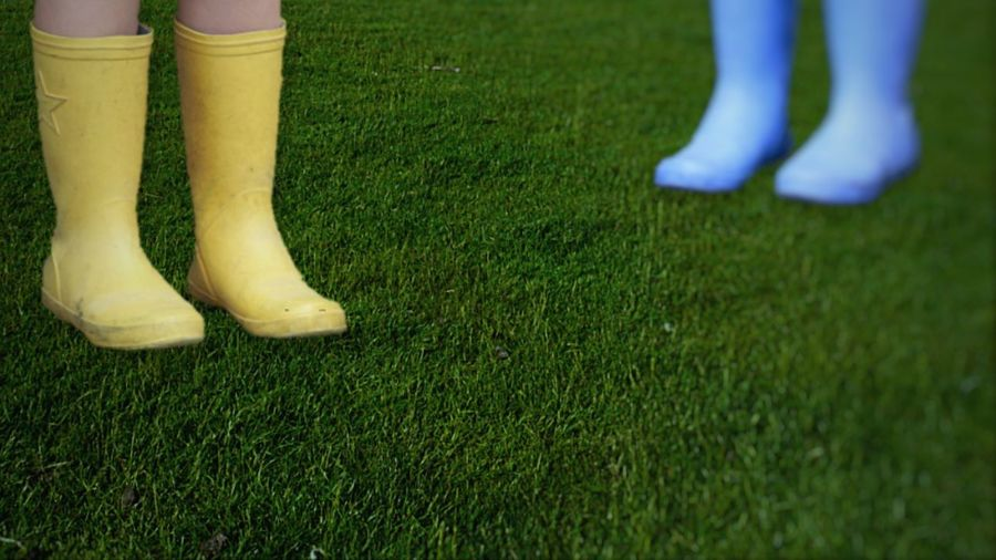 Low section of friends wearing rubber boots on grassy field