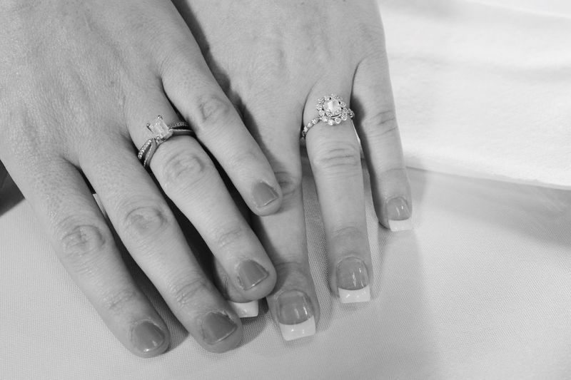 Cropped hands of brides wearing wedding rings
