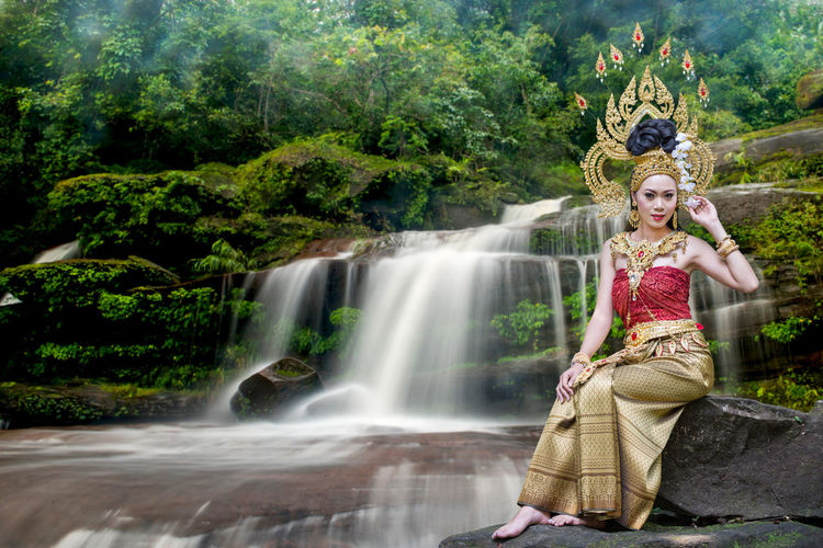 Portrait of beautiful young woman wearing crown and traditional clothing while sitting against waterfall in forest