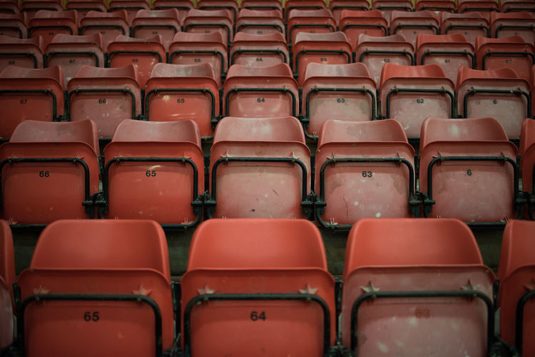 Repetition Absence Abundance Arrangement Arts Culture And Entertainment Auditorium Backgrounds Chair Empty Full Frame In A Row Indoors  Large Group Of Objects No People Order Red Repetition Seat Side By Side Sport Stadium