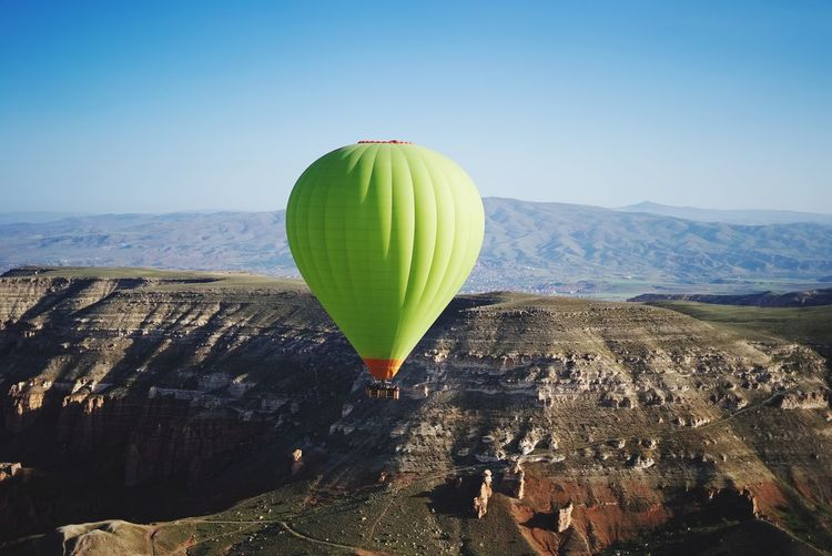 Hot air balloon flying over mountain against sky