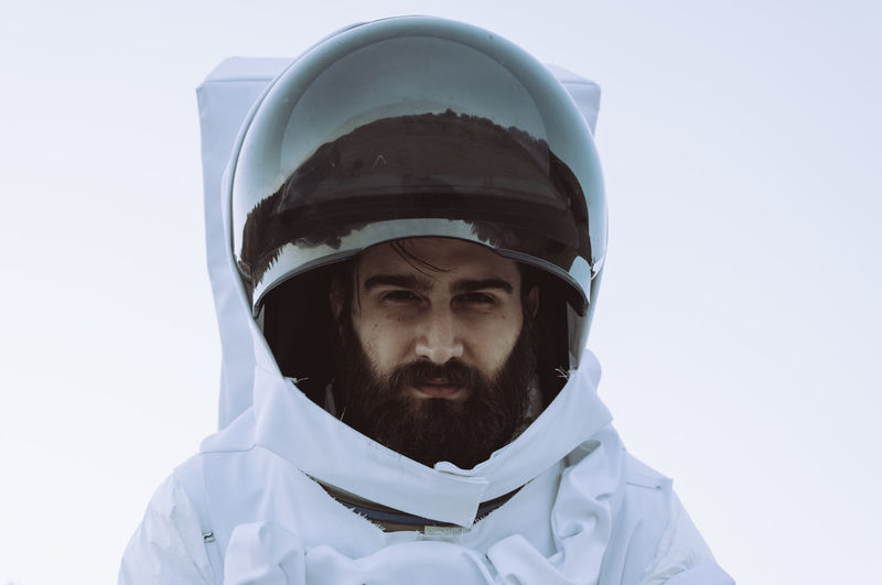 Portrait Of Young Man In Astronaut Costume Against White Background