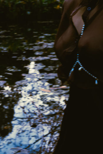 Midsection of woman standing by lake