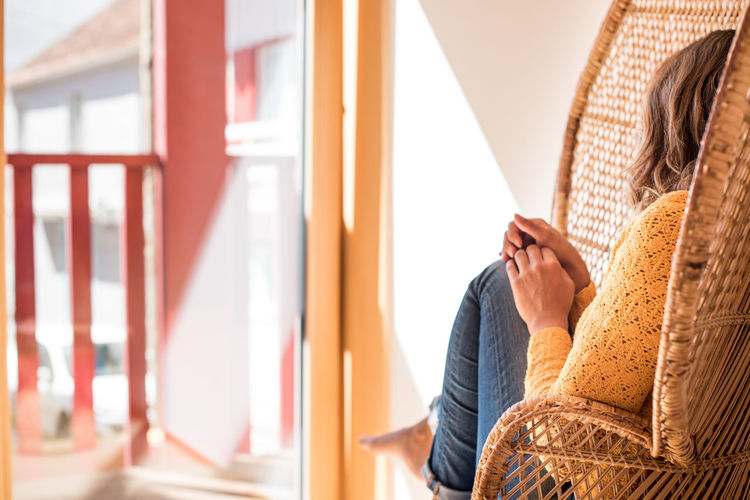 Midsection of woman sitting on seat at home