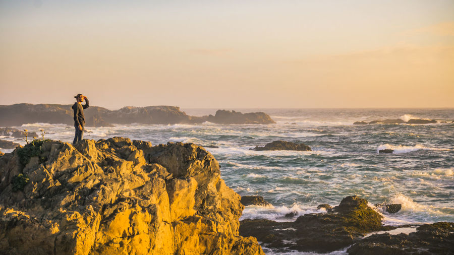 Looking at the sunset over a rocky shoreline Rock Rock - Object Sea Solid Sky One Person Beauty In Nature Leisure Activity Standing Lifestyles Scenics - Nature Water Nature Real People Full Length Land Rock Formation Horizon Over Water Outdoors Looking At View Waves Crashing Waves Crashing On Rocks Sunset