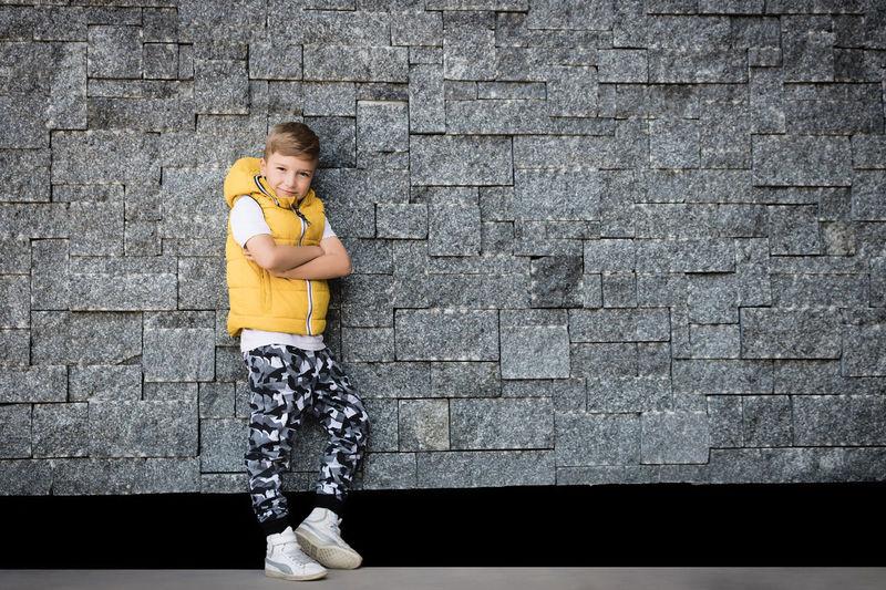 Full length portrait of girl against wall
