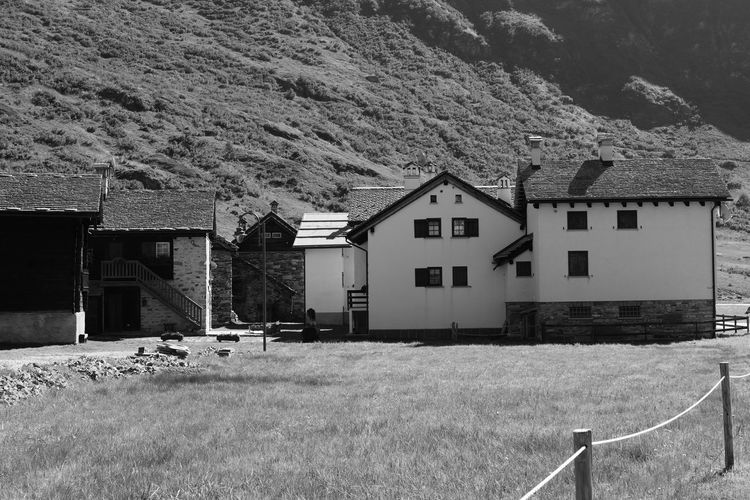 House on field by houses against mountain