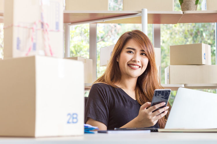 Portrait of smiling young woman using phone while sitting on table
