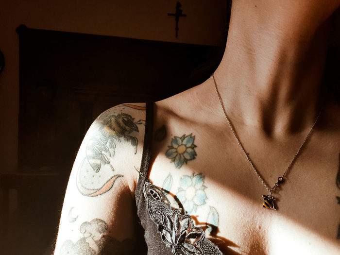 Midsection of sensuous woman with tattoo at home