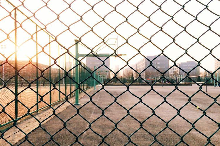 Basketball hoop seen through chainlink fence against sky