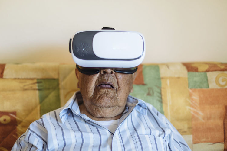 Man wearing virtual reality simulator at home