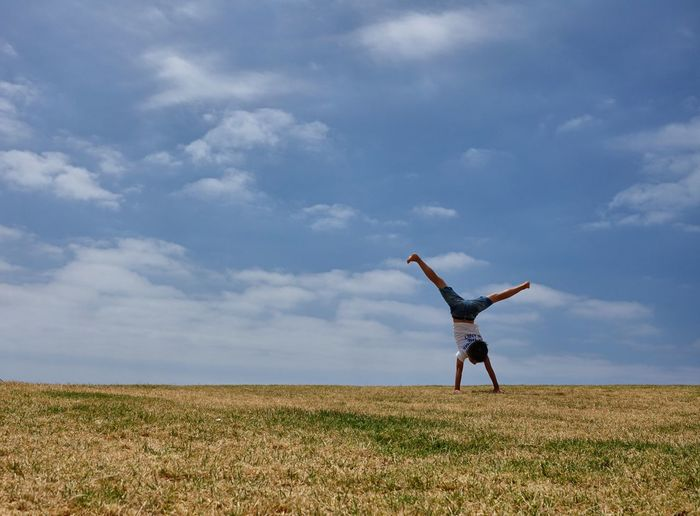 Boy doing a cartwheel on a hill against cloudy sky