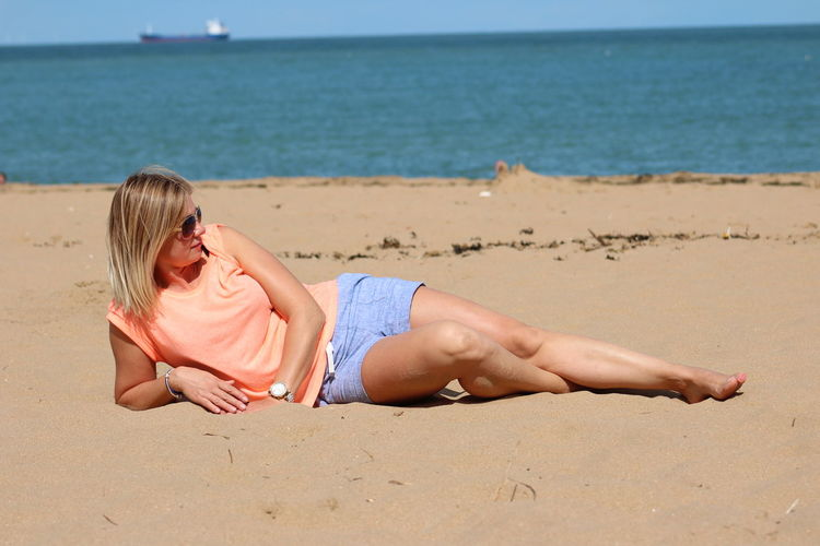 Full length of mid adult woman lying at beach