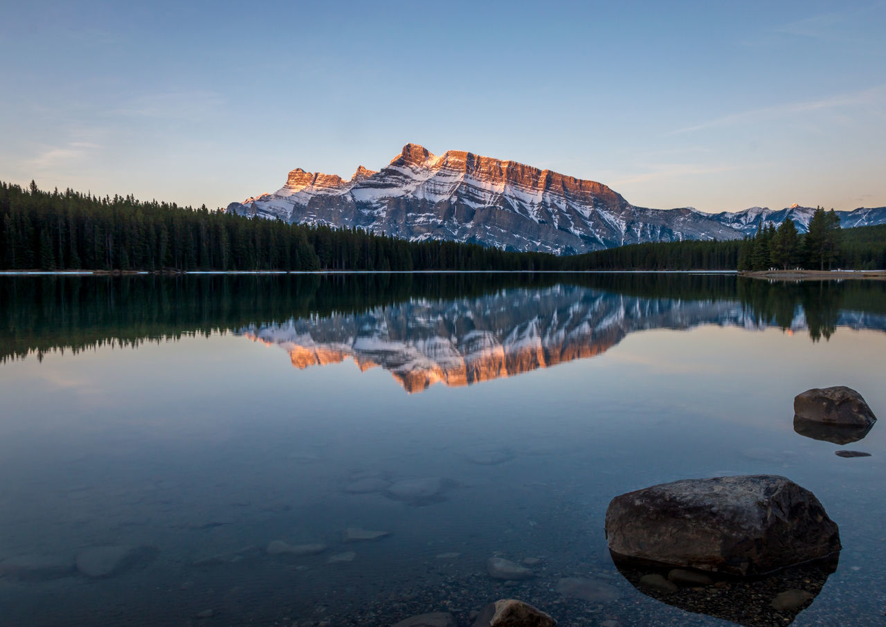 Calm lake against rocky mountains