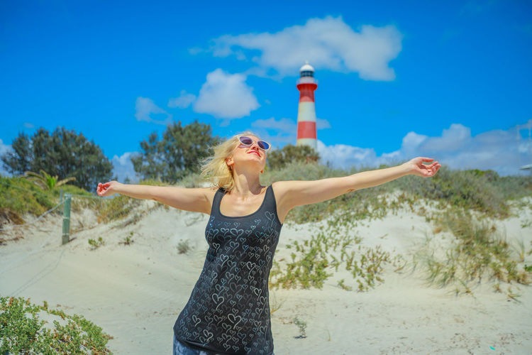 Woman with arms outstretched standing against lighthouse
