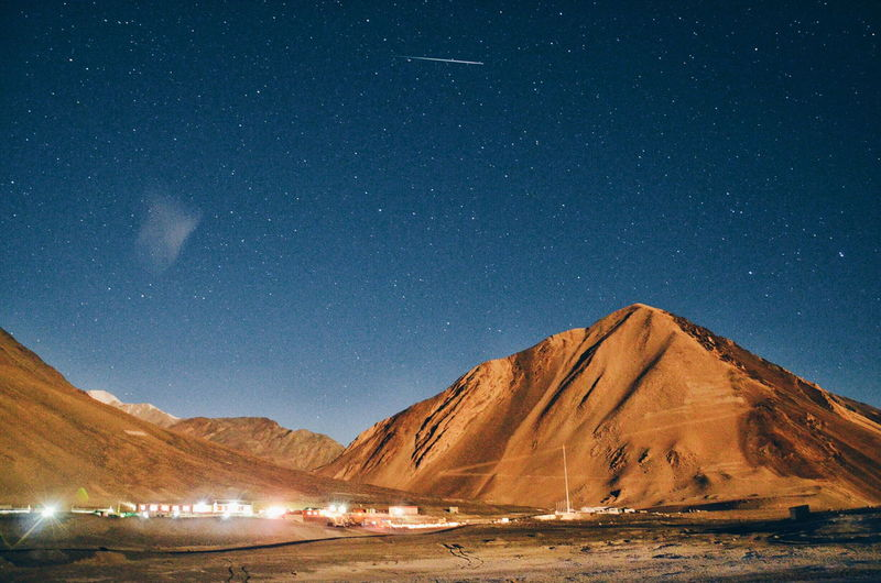 Scenic view of illuminated mountains against sky at night