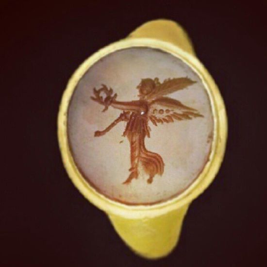 A Roman Gold AND Carnelian Ring CIRCA 1ST CENTURY B.C. The hollow gold hoop widening at the shoulders to a circular bezel, the large circular carnelian intaglio with the winged figure of flying Victory facing left, her left leg straight, right leg kicked out with drapery billowing behind, holding a wreath in her outstretched left hand and a palm branch in her right Intaglio Ancient Ancientjewelry Jewelry Jewellery Jewelblog Fashioninsta Jewelleryindetail Jewelryaddiction Jewelryaddict Joias Archaeology Arkeoloji Turkishfollowers