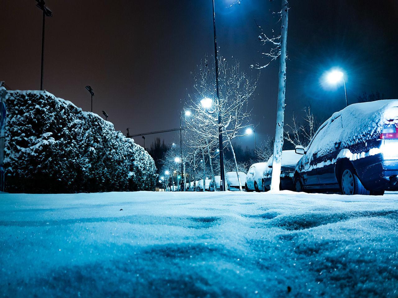 CARS ON ILLUMINATED ROAD IN WINTER AT NIGHT