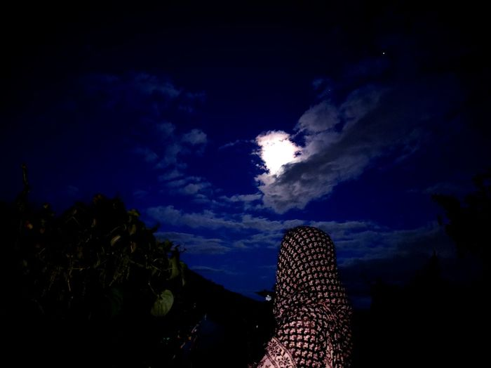 Low section of woman against sky at night