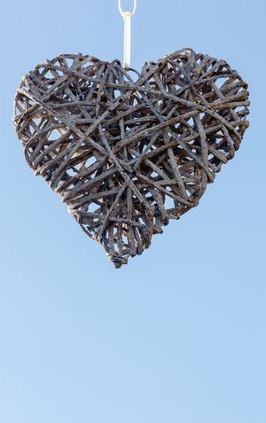 Hanged heart made from woven wooden sticks on solid light blue sky background. Vertical email composition with bottom text space Background Blue Communication Day Evidence Handmade Hanged Heart High Innovation Jesus Christ Love Mothers Day No People Passion Proof Redemption Religion Romance Single Flower Sky Stick Unique Valentine's Day  Woven Pattern