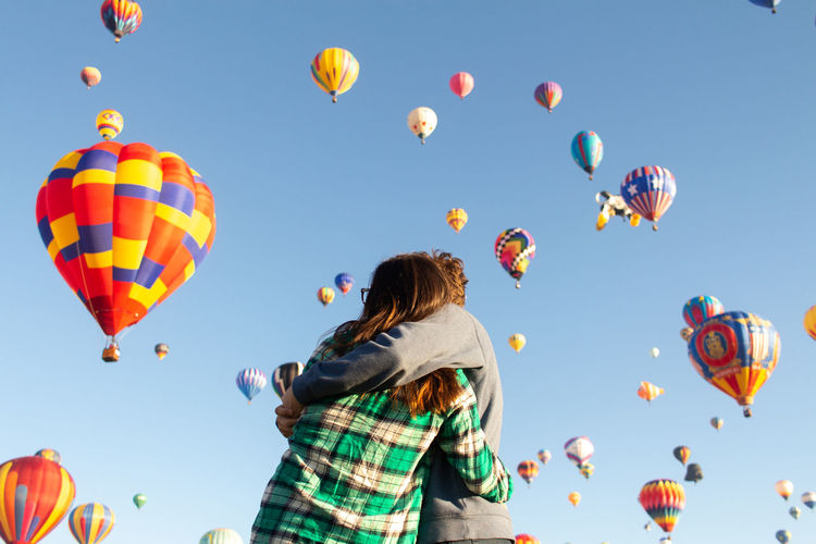 Low angle view of couple embracing against hot air balloons in sky