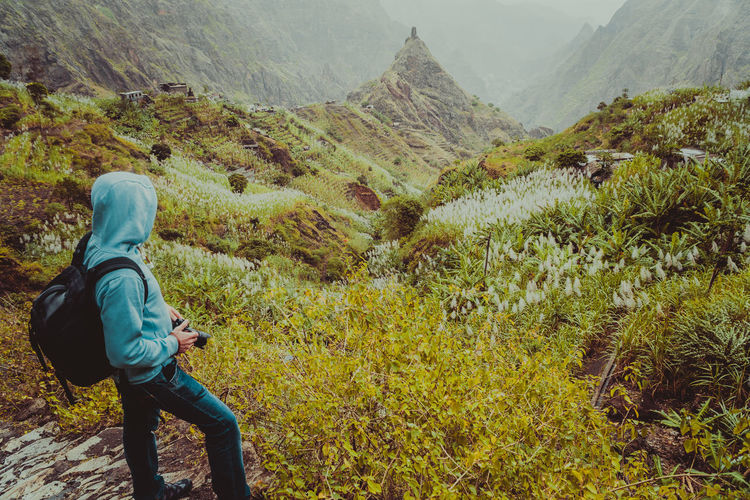 Traveler with backpack looking for motive of rural landscape with mountain peaks and ravine in dust air on the path from Xo-Xo Valley. Santo Antao Island, Cape Verde Cape Verde Trekking Activity Adventure Beauty In Nature Day Environment Green Color Hike Hiker Hiking Hood - Clothing Leisure Activity Lifestyles Mountain Mountain Range Nature Non-urban Scene One Person Outdoors Plant Real People Scenics - Nature Tranquil Scene Valley