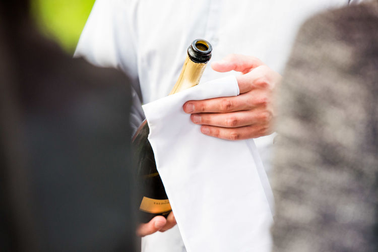 Midsection of man holding wine bottle