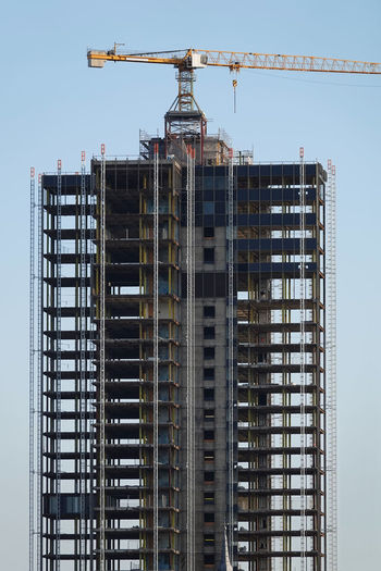 Low angle view of crane by building against clear sky