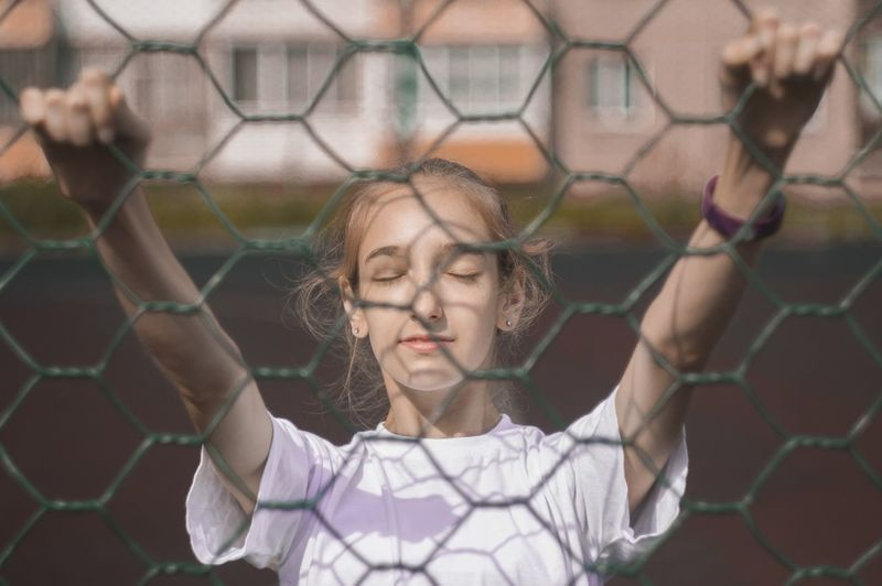 Girl with closed eyes seen through chainlink fence