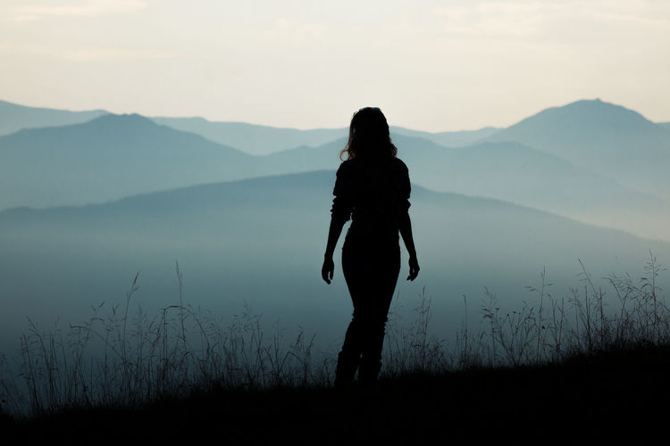 Rear view of silhouette woman standing on mountain against sky