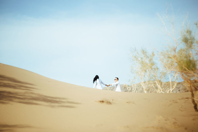 Mid distance view of couple holding hands at desert against blue sky