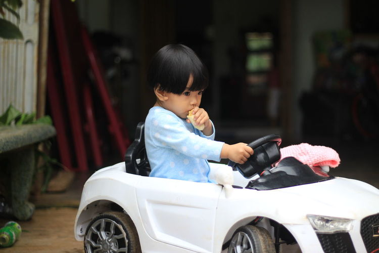 Cute girl eating food while sitting in toy car