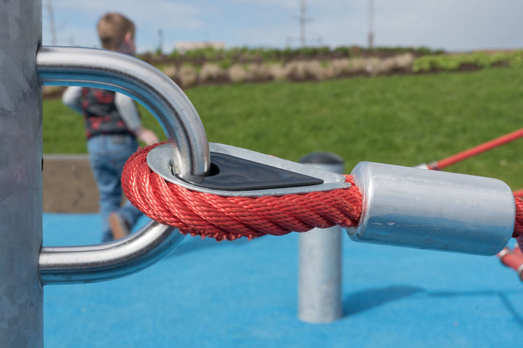 Focus On Foreground Metal Day Close-up Nature Red Equipment Outdoors No People Park Strength Railing Park - Man Made Space Handle Sunlight Sport Grass Blue Water Outdoor Play Equipment