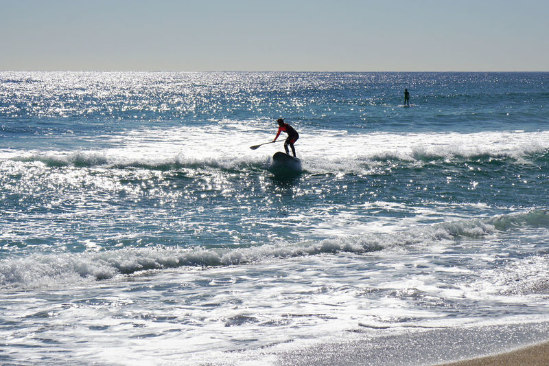 Stand up paddle surfing or boarding (SUP) Aquatic Sports Backlight Barcelona Barceloneta Beach Holiday Leisure Activity Lifestyles Mediterranean  Nature Ocean Real People Blue Wave Silhouette Stand Up Paddle Surfing Stand Up Paddling Summer Sup Surf Surfboard Vacation Water Water Sports Wave