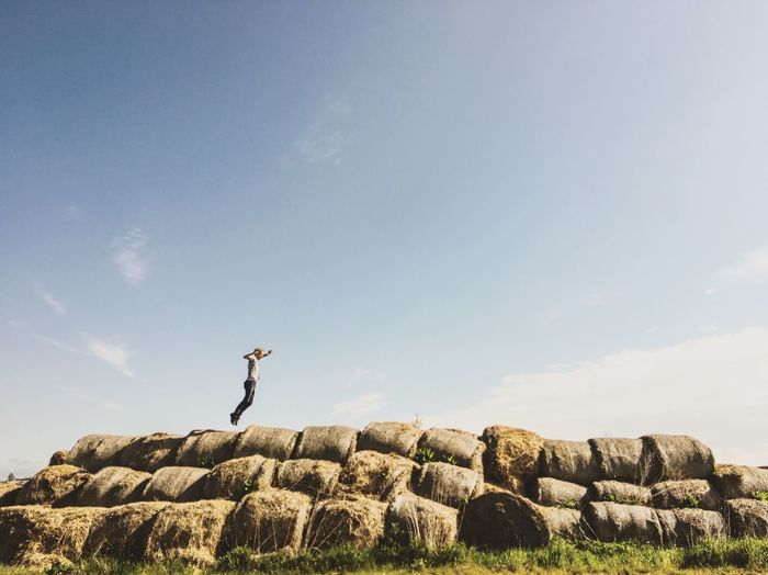 Man Jumping On Hay Bales Against Sky