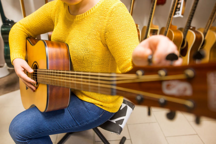 Midsection of woman playing guitar at store