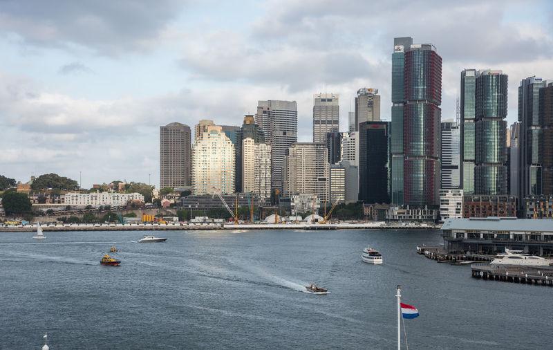 Boats In Sea Against Modern Buildings In City