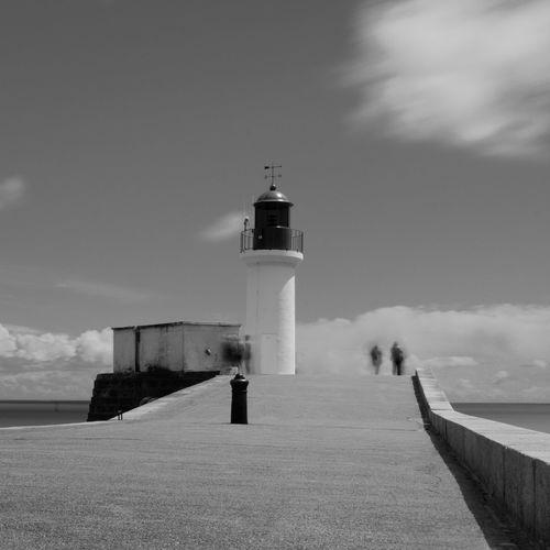 Lighthouse on footpath by sea against sky