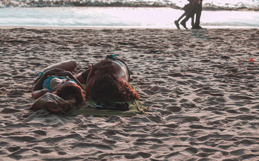 Couple lying at beach during sunset