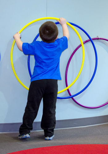 a young boy removes a plastic hoop of a wall, to try and seeif he can make it move Hula Hoops Active Kids Blue Casual Clothing Circle Full Length Holding Human Arm Indoors  Leisure Activity Lifestyles Multi Colored One Person Plastic Hoop Platic Play Playground Playing Real People Rear View Skill  Standing Toy Yellow