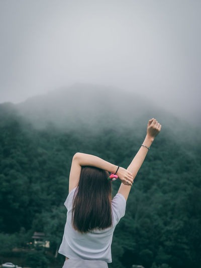 Rear view of woman with arms raised standing in fog