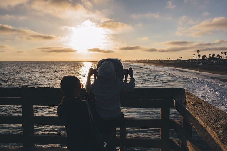 Rear view of mother standing by child using coin-operated binoculars by sea against sky during sunset