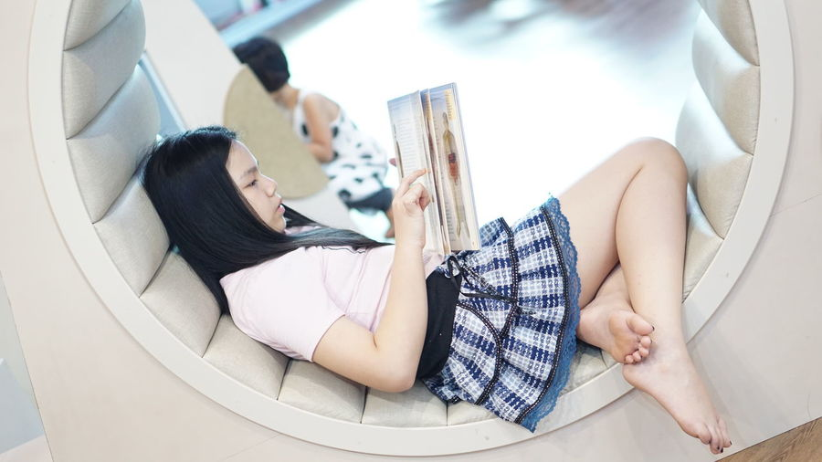 High angle view of woman sitting on book