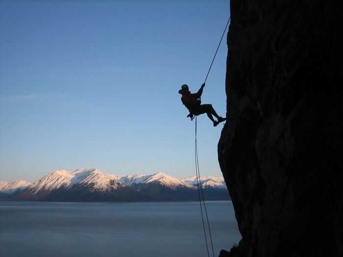 Man rock climbing on cliff against clear blue sky