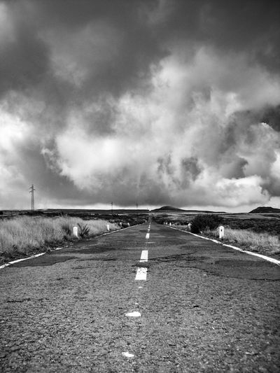 Road passing through landscape against cloudy sky