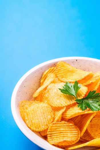 Fried corrugated golden potato chips with parsley leaf in wooden bowl on blue background