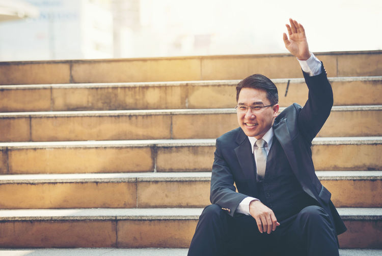 Businessman gesturing while sitting on steps