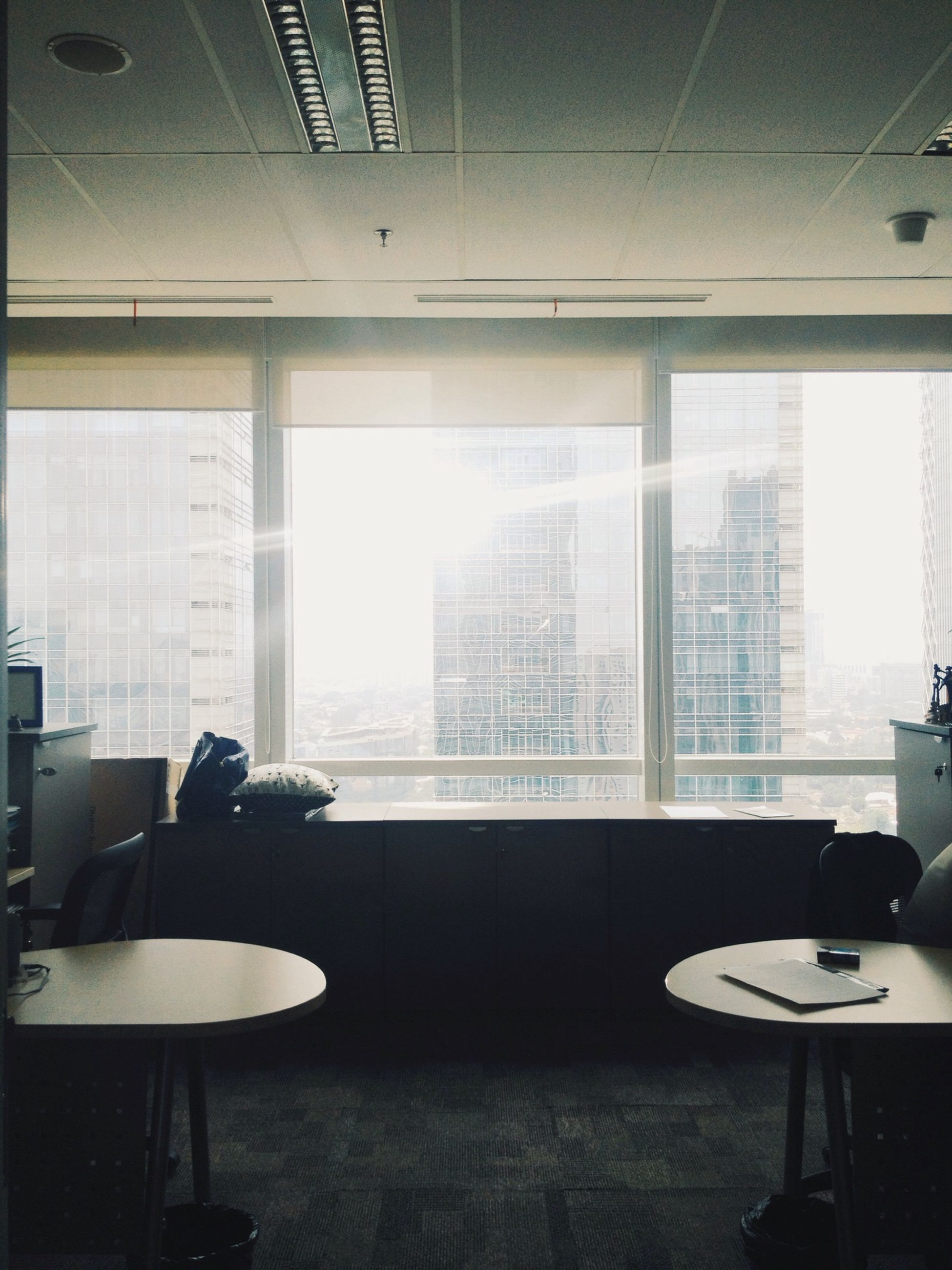 indoors, window, chair, glass - material, empty, home interior, architecture, absence, table, transparent, built structure, domestic room, office, modern, interior, reflection, sunlight, day, restaurant, glass